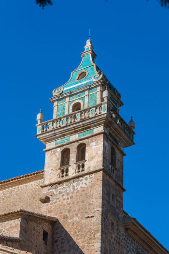 Beautiful view. Tower of the monastery in Valldemossa. Close to the Sierra de Tramuntana. Architecture Building Exterior Built Structure Sky Blue Low Angle View Building Tower Clear Sky No People Nature Travel Destinations History The Past Place Of Worship Belief Religion Sunlight Day Spirituality Clock Spire  #NotYourCliche Love Letter