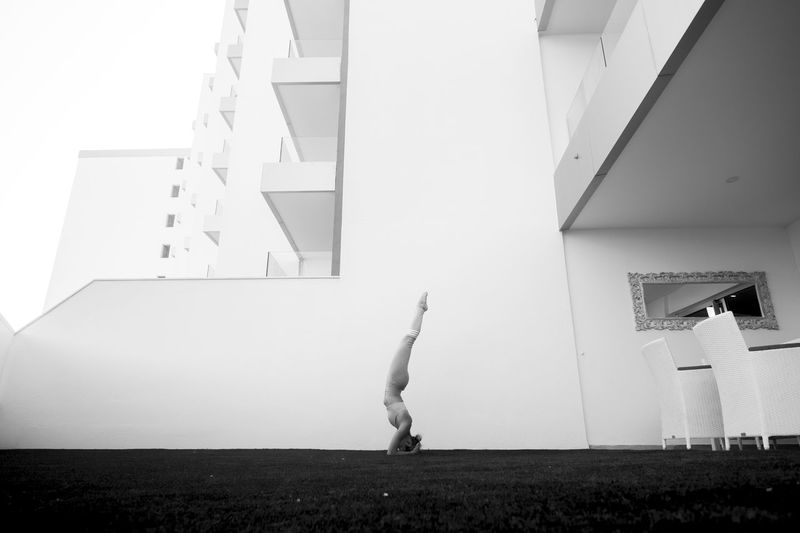 black and white image fine art representing beautiful thin babe female young athlete doing yoga and pilates positions outside home in a garden with all the building in background. line light and shadow, nice composition Yoga Architecture Arms Raised Building Exterior Built Structure Day Full Length Healthy Lifestyle Human Arm Jumping Leisure Activity Lifestyles Nature One Person Outdoors Practicing Real People Side View Sport Staircase Strength Walking Wall - Building Feature White Color Women