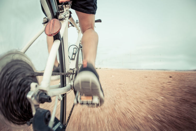 Low section of man riding bicycle on sea