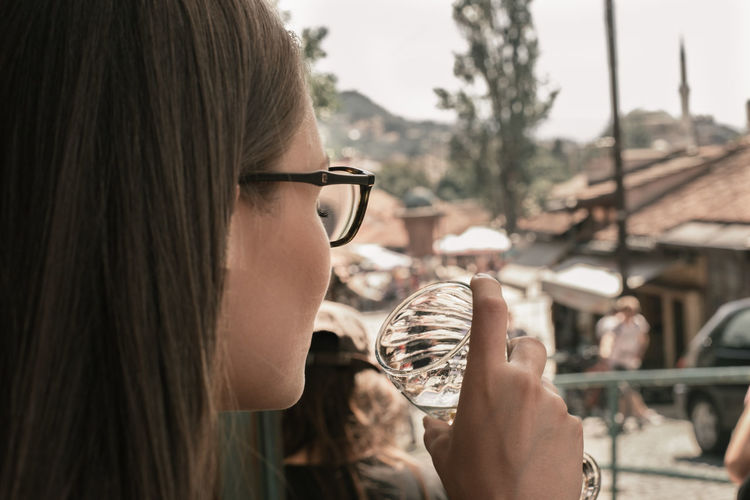 Close-up of young woman drinking outdoors