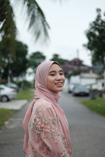 Portrait of teenage girl standing on road