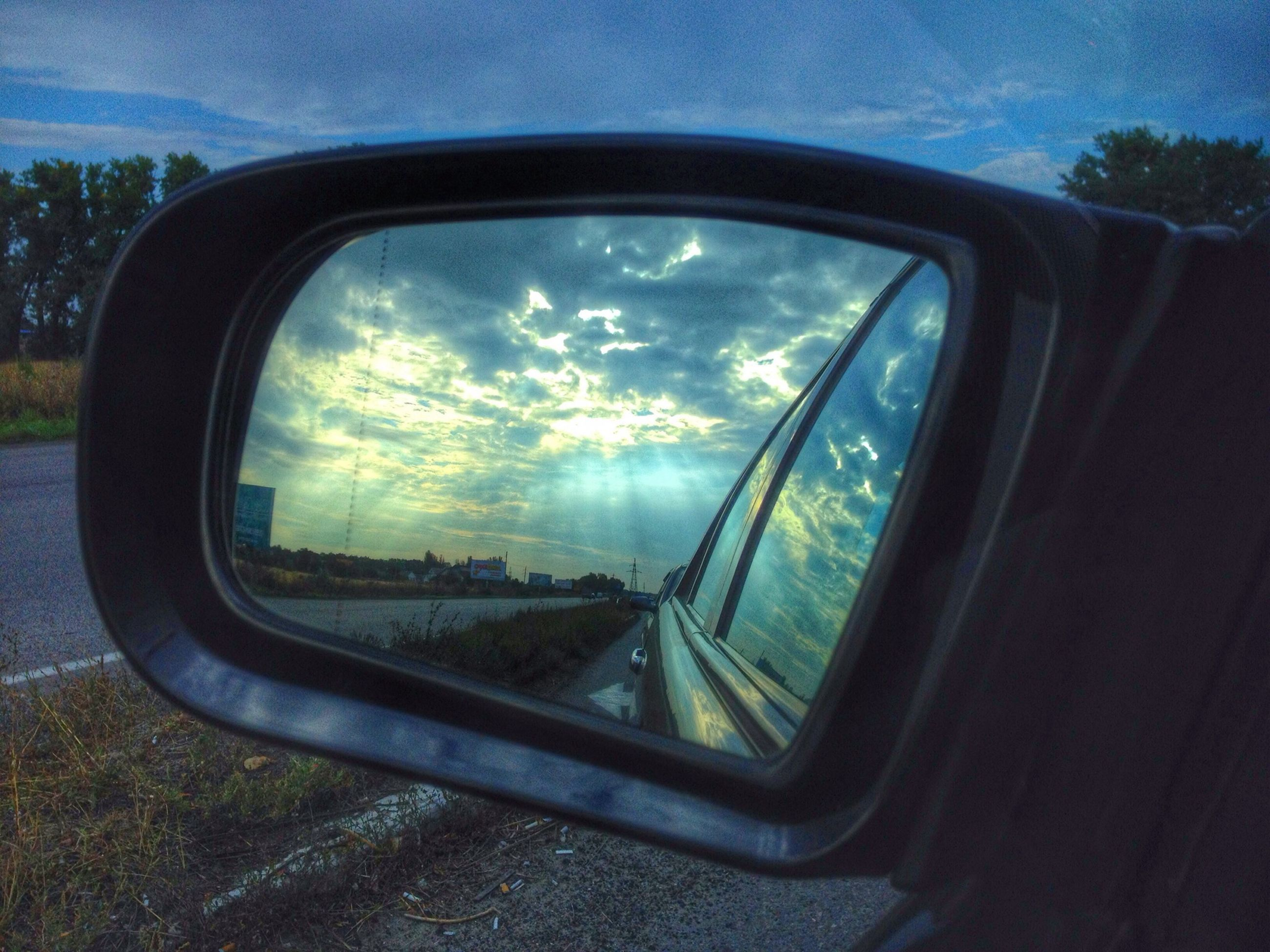 transportation, glass - material, sky, car, transparent, mode of transport, side-view mirror, land vehicle, cloud - sky, window, vehicle interior, reflection, cloud, road, part of, sunlight, landscape, car interior, sun, tree