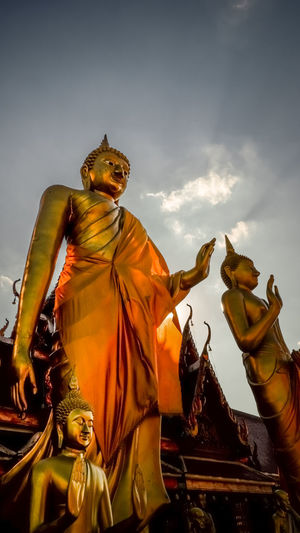 Low angle view of angel statue against temple against sky