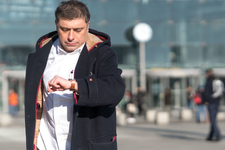 Man Checking Time While Standing Against Building