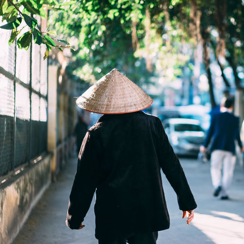 .... Hat Adult Asian Style Conical Hat City Day Focus On Foreground Full Length Hat Lifestyles Men One Person Outdoors People Real People Rear View Travel Destinations Tree Walking Women