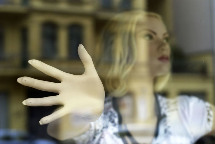 Close-up of mannequin on window display at shop