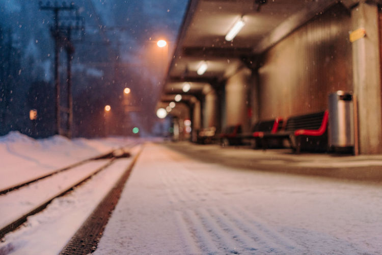 Empty train station in suiss mountains during snow fall Illuminated Transportation Rail Transportation Mode Of Transportation Street Track Night City Architecture Lighting Equipment Railroad Track No People Public Transportation Cold Temperature Snow Land Vehicle Train Street Light Direction Snowing Surface Level