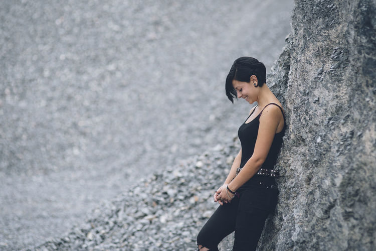 Caucasian young woman wearing black clothes beautiful brunette girl leaning against gray rock wall outdoors. Beautiful Woman Casual Clothing Contemplation Day Focus On Foreground Hairstyle Leisure Activity Lifestyles Looking One Person Outdoors Real People Rock Rock - Object Side View Solid Standing Three Quarter Length Women Young Adult Young Women