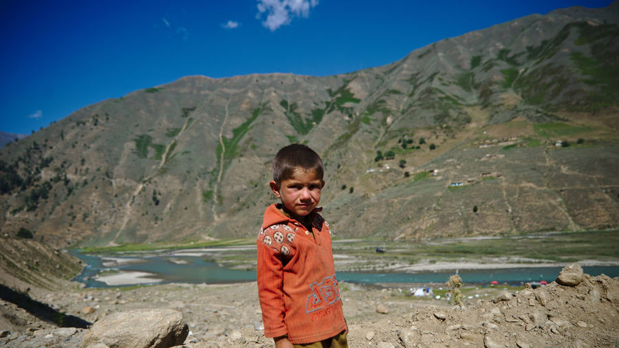 Portrait of boy standing on mountain against sky