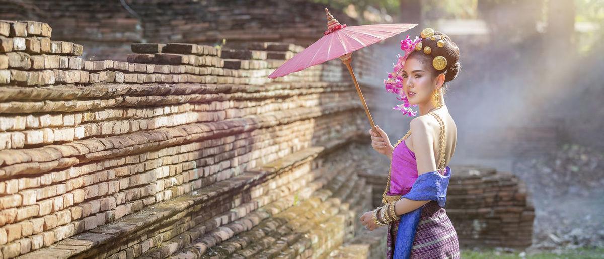 Full length of girl standing against pink wall