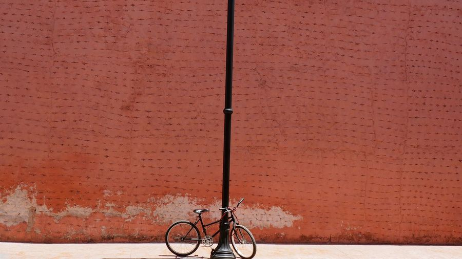 Bicycle Parked By Pole Against Brown Wall