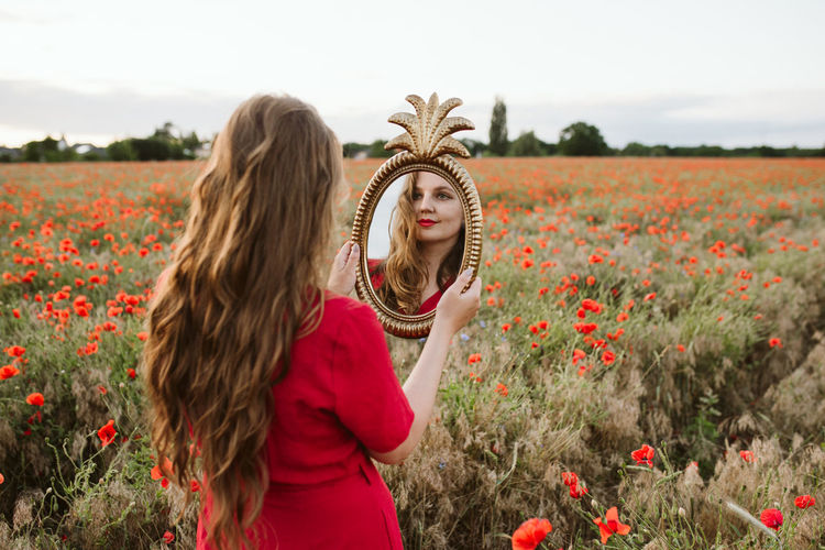 Beautiful young woman by poppy flowers on field against sky