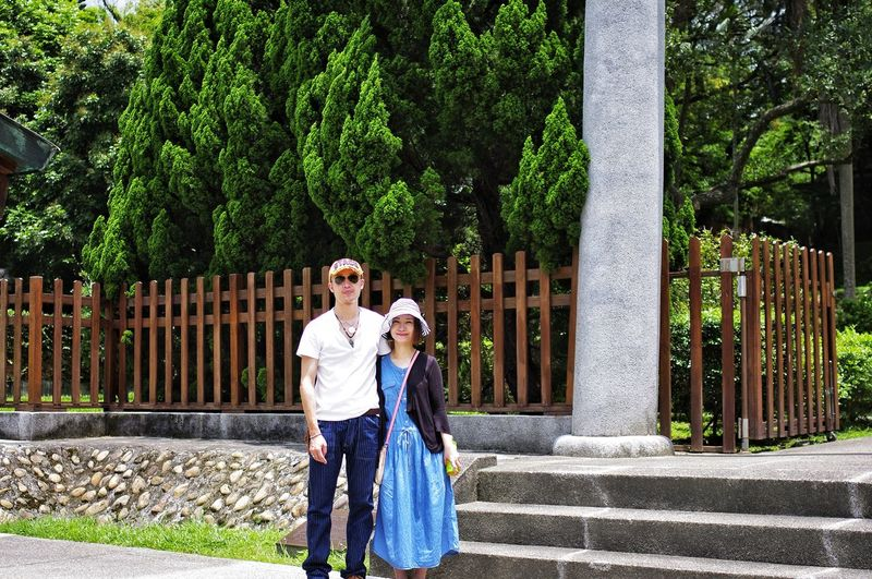 Couple standing against fence at park