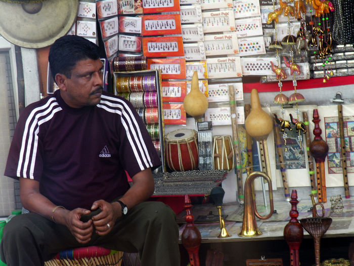 Guy running musical instrument shop in Delhi, India. Cymbals Delhi Drums Flutes India Musical Instruments Retail  Shopkeepers Shops Tabla Trumpets