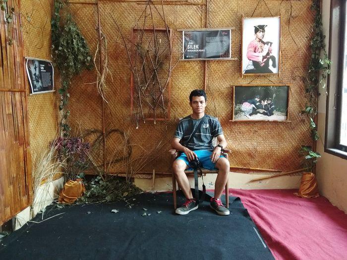 Full length of a boy sitting on wall