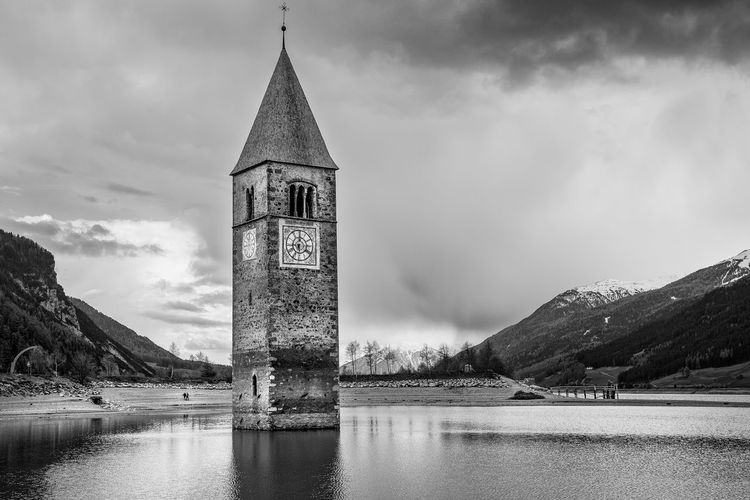 Abandoned Tower Amidst Lake Against Cloudy Sky