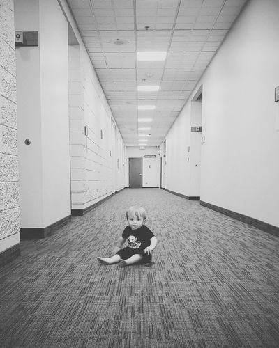 Boy sitting on floor in corridor