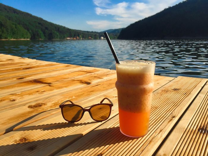 Glass of orange smoothie with drinking straw with a pair of sunglasses on a rustic wooden pontoon
