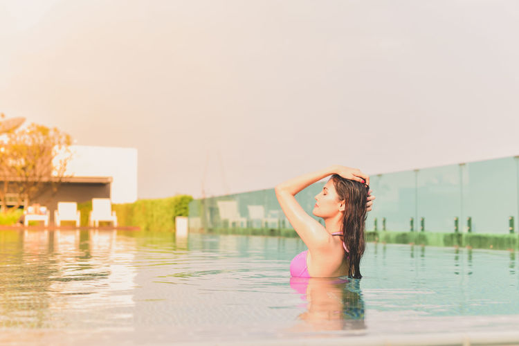 Side view of woman swimming in pool against clear sky