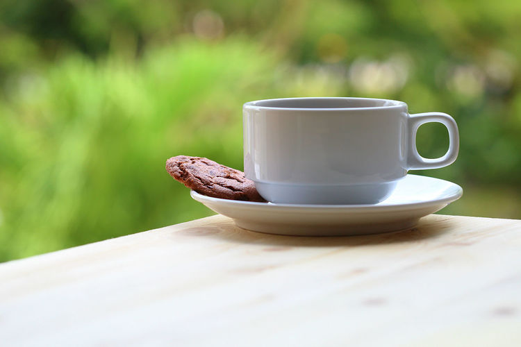 Meal time with a cup of coffee or tea with chocolate cookie placed on wooden table. Beautiful Bokeh Breakfast Cappuccino Close-up Coffee Coffee - Drink Coffee Cup Coffee Time Cookie Cup Day Drink Food Food And Drink Foodphotography Green Color Meal Natural No People Outdoors Porcelain  Table Tea White Color