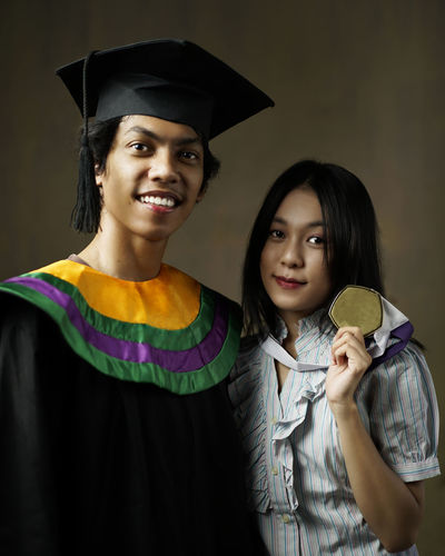 Portrait of friends wearing graduation gown and medal