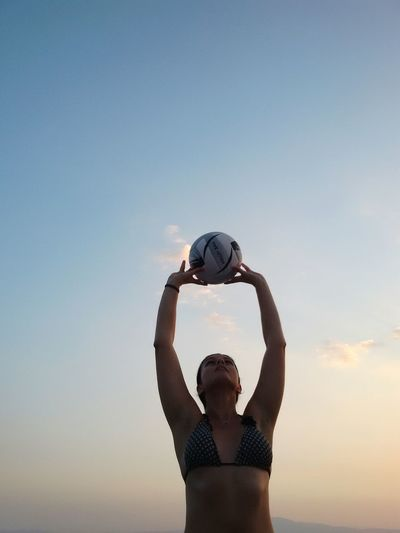 Young woman in bikini playing beach volleyball against sky