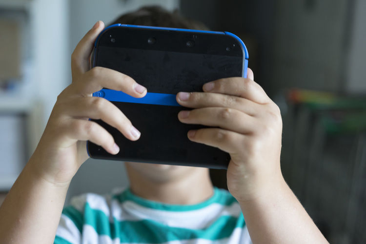Close-up of boy holding video game in front of his face
