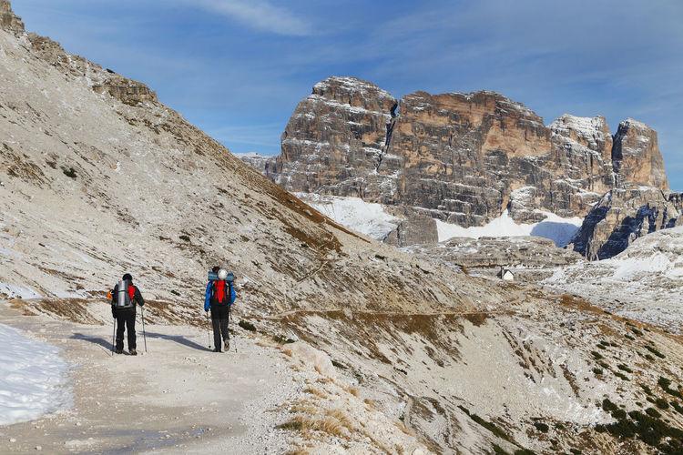 People Walking On Rocky Mountain Against Sky