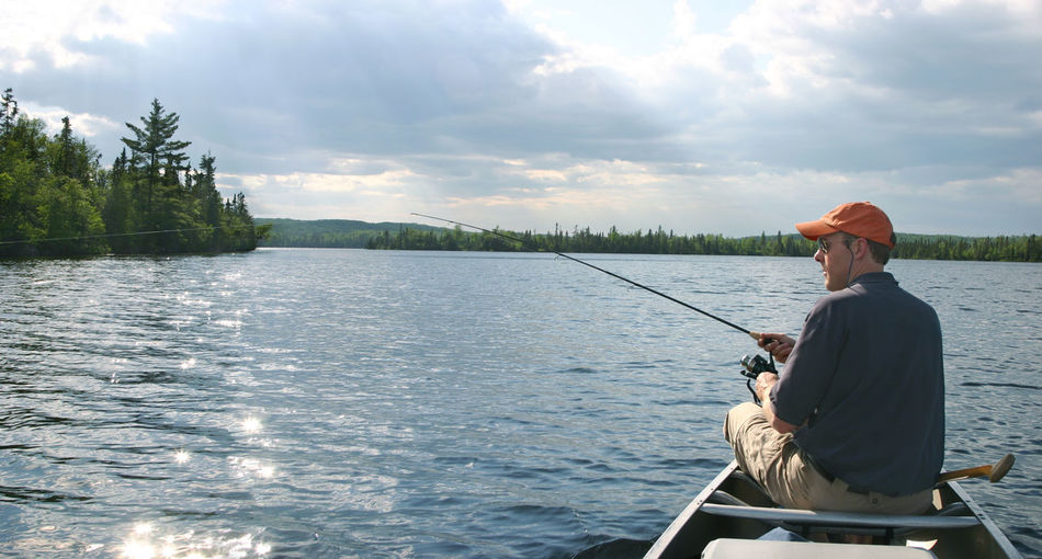 Rear view of man fishing in water against sky