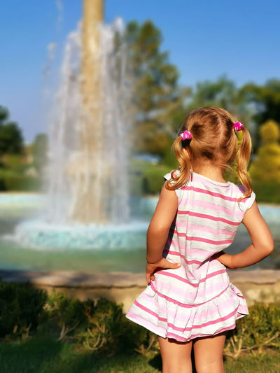 Rear view of girl looking at fountain in park