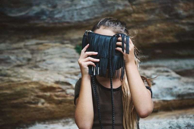 Close-up of woman hiding face behind purse against rock formation