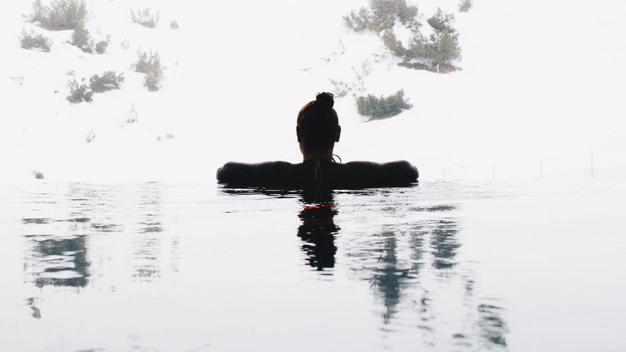 Man sitting in lake against sky