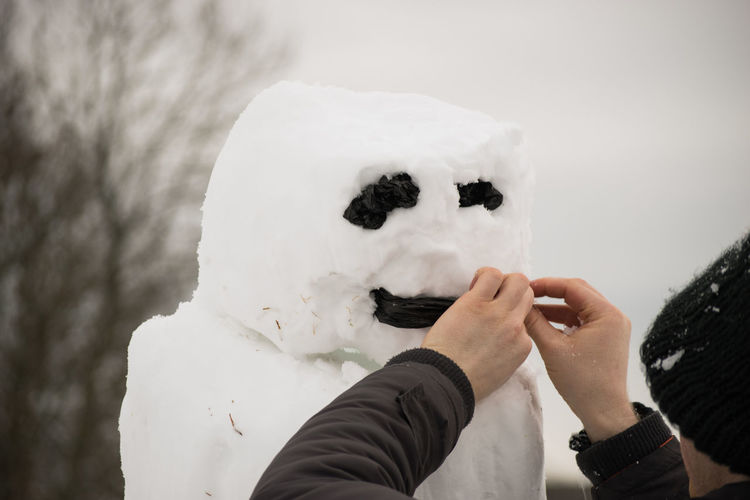 Close-Up Of Man Making Snowman