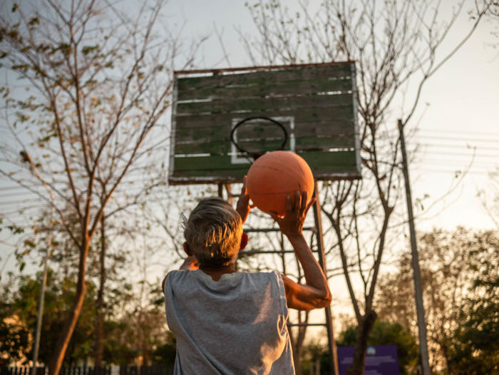 Rear view of senior man playing with basketball in court