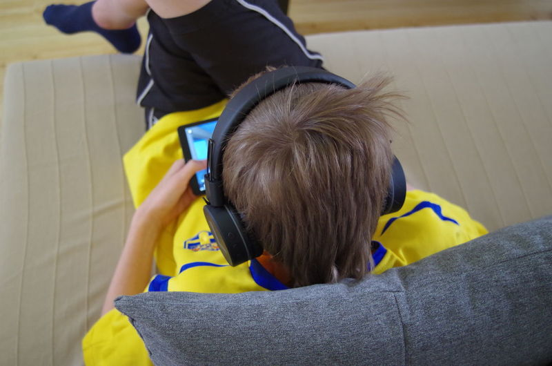 A young boy playing his favourite game on his tablet Boys Child Childhood Communication Connection High Angle View Holding Home Interior Indoors  Leisure Activity Lifestyles Males  Men One Person Real People Rear View Technology Wireless Technology Yellow
