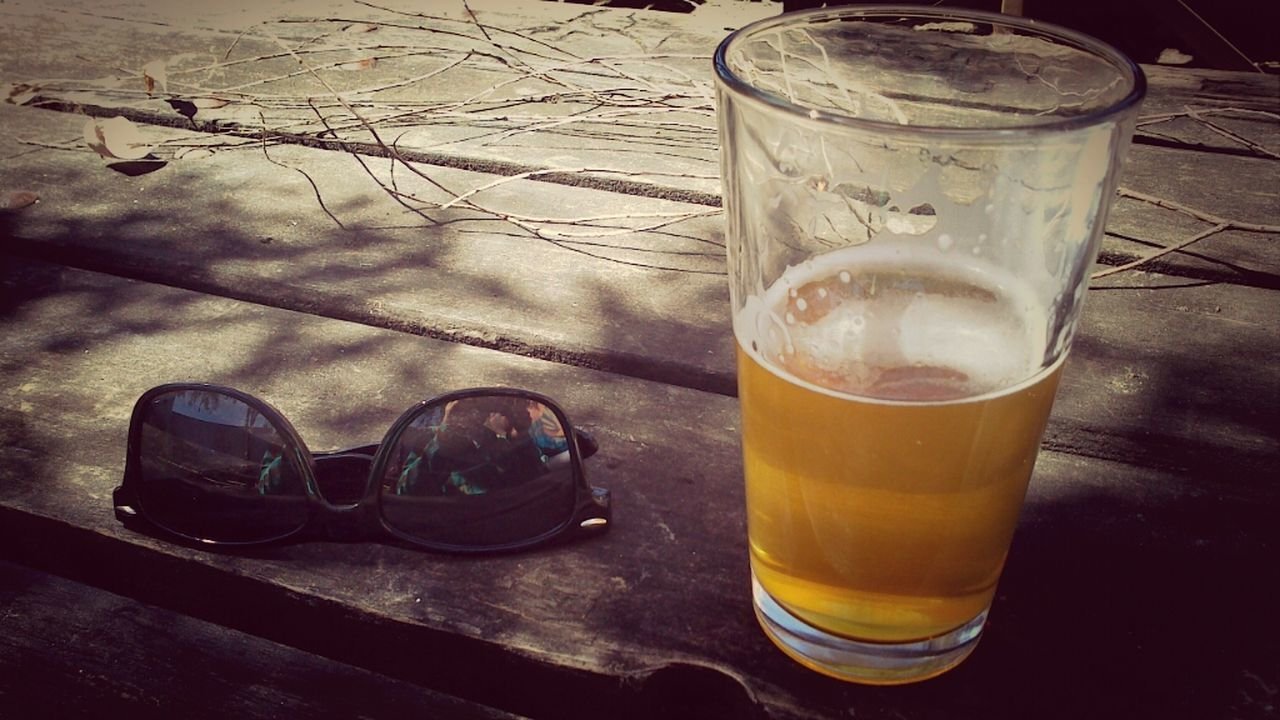 Close-Up Of Beer In Glass By Sunglasses On Table