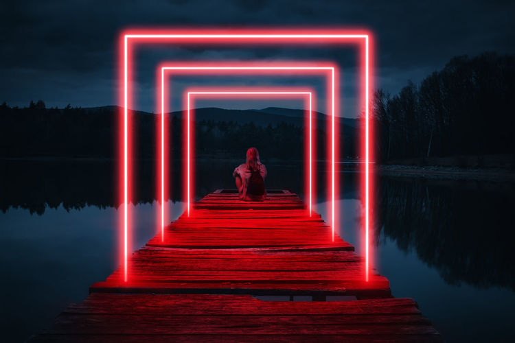 Woman standing by lake at night