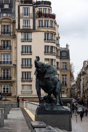 Statue against buildings in city