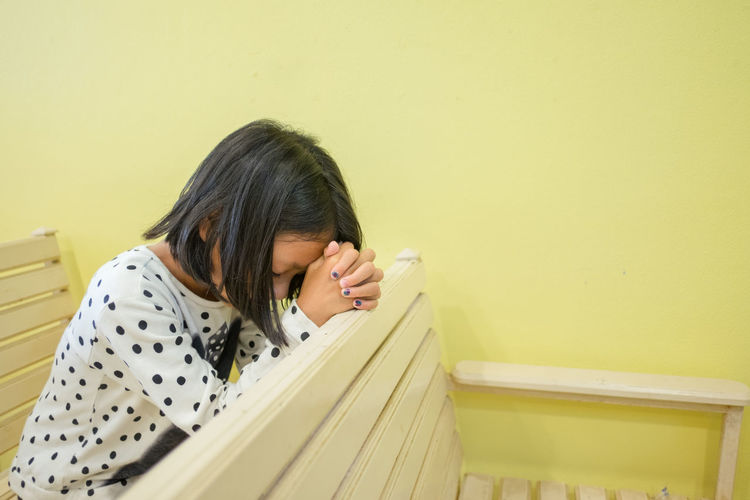 Girl Praying While Sitting On Pew At Church