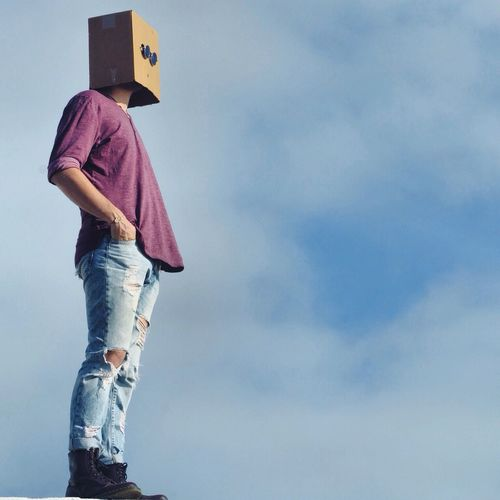 Low angle view of man wearing cardboard box on head against sky