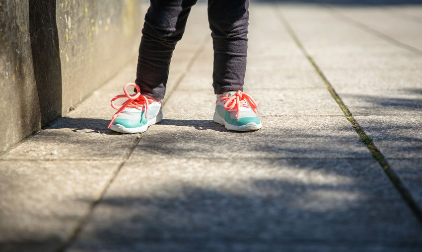 Low section of girl standing on footpath