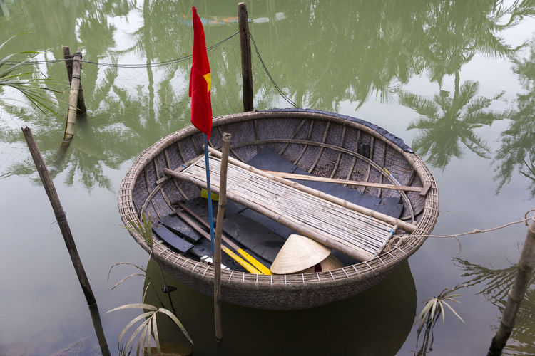 Moored small traditional round wicker fishing boat with Vietnamese flag, oars and bamboo seat, Cam Nam, Hoi An, Vietnam Hoi An, Vietnam Cam Nam Water Nautical Vessel Mode Of Transportation Outdoors Moored No People Round Boat Traditional Vietnamese Wicker Fishing Boat Oars Flag Bamboo Seat Canal Reflection Transportation Tree Day Rowboat