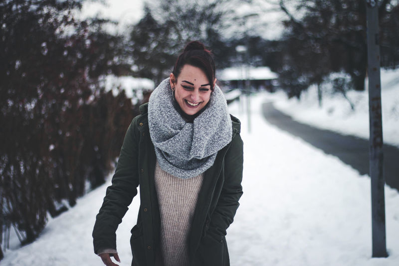 Smiling young woman walking on snow covered land