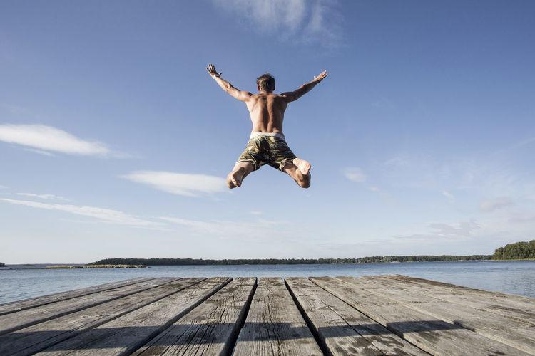 Man jumping in sea against sky