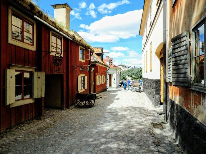 Street Amidst Houses Against Sky