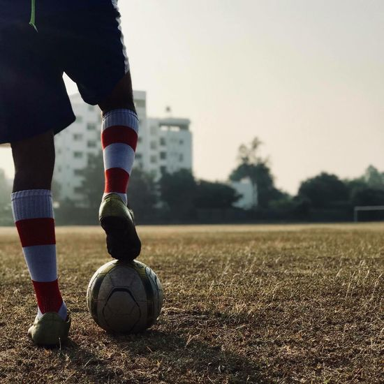 Low section of player standing on soccer field