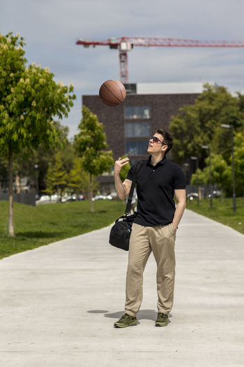 Athletic male model wearing sunglasses and casual clothing walking in an urban park with a basketball and sports bag on his shoulder. Long shot. Adult Basketball Footpath Khaki Pants Long Shot Man Sunny Afteroon Buildings Casual Clothing Caucasian Day Golf Shirt Good Looking Handsome Male Model Outdoors Outside Portrait Posing Shoulder Bag Summer Sunglasses Urban