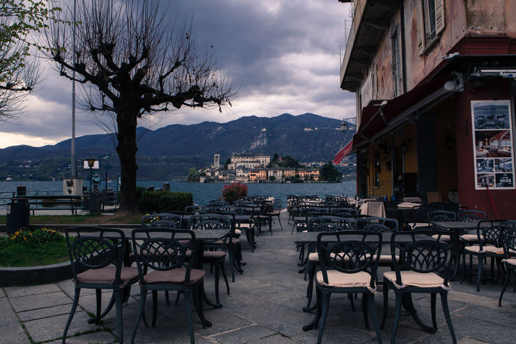 Orta San Giulio, Piedmont, Italy. Views of St. Julius' Island, in the middle of Lake Orta, with its ancient cloistered monastery, taken from the village's main square. Borghiditalia Borghitalia Chair Cloudy Historic Historical Building History Island Italy Lake Lake View Lakeside Landscape Monastery Old Town Orta  Orta S.Giulio Orta San Giulio Piedmont Seat Table Travel Tree Village Life Water