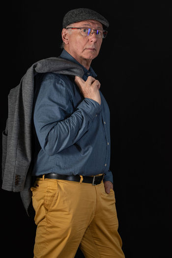 Portrait of man with jacket standing against black background