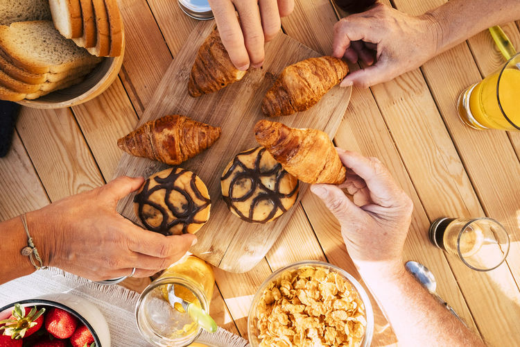 Cropped hands of people having sweet food over table in cafe